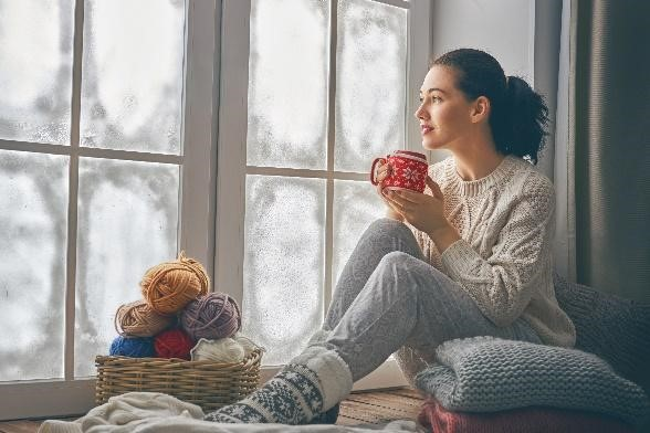 afbeelding van vrouw met een kop thee die door ruiten van dubbel glas naar buiten kijkt.
